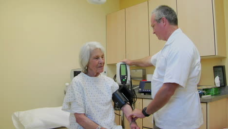 A-medical-professional-takes-the-blood-pressure-of-an-elderly-patient