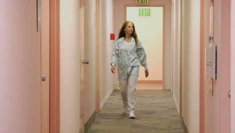 A-medical-professional-walks-down-the-hallway-of-a-medical-facility