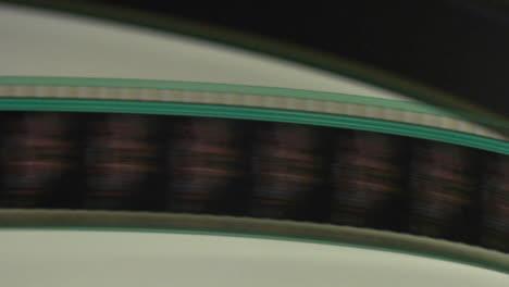 Un-Carrete-De-Tira-De-Película-A-Través-De-Un-Proyector-En-Esta-Toma-Abstracta