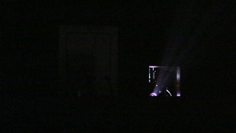 Light-shines-from-a-projector-into-a-darkened-theater
