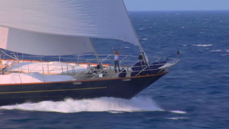 A-woman-raises-her-arms-in-victory-on-the-bow-of-a-large-sailboat