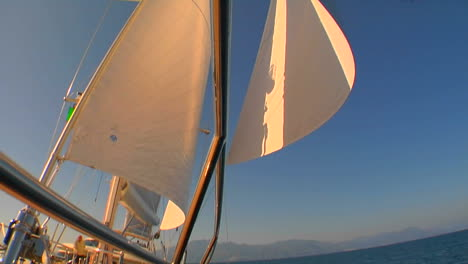 A-pan-across-a-sailboat-in-the-Mediterranean-as-we-tilt-up-to-view-the-white-sails