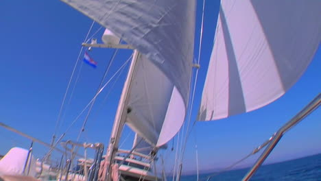A-sailboats-deck-as-it-moves-across-the-ocean-and-tilt-up-to-sails