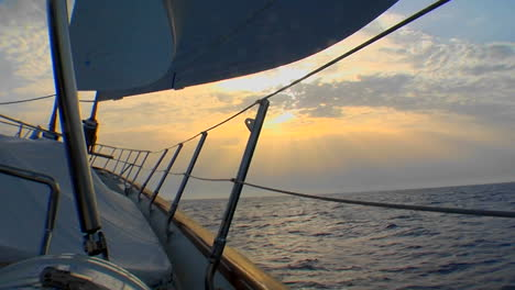A-shot-of-the-side-of-a-sailboat-heading-into-the-sunset