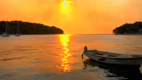 A-small-boat-gently-floats-as-a-Croatian-sunset-transpires