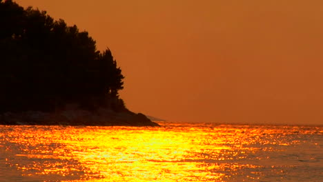 A-Croatian-sunset-is-reflected-on-the-ocean-trees-blow-in-the-background