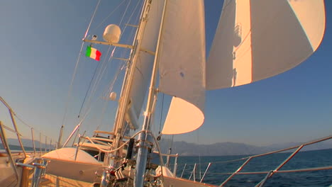 View-of-sails-on-sailboat-from-deck-as-the-wind-fills-them-Pan-down