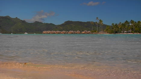 Low-angle-of-Tahitian-beach-huts-in-the-distance-as-waves-lap-the-shore
