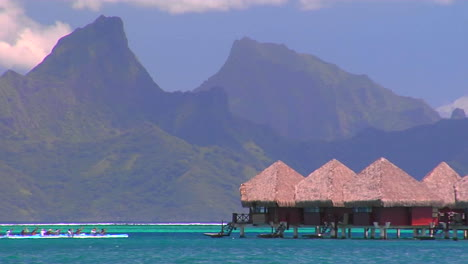 Tahitian-huts-on-the-water-with-mountain-peaks-in-the-background-as-rowers-pass-by