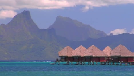 Tahitian-huts-on-the-water-with-sharp-mountain-peaks-in-the-background-and-an-airplane-passes-through