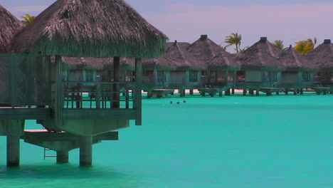 Tahitian-huts-rest-over-turquoise-water-Slow-zoom-in