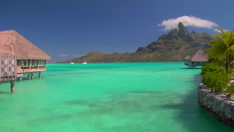 Tahitian-huts-rest-over-turquoise-water-as-small-boat-passes-through-and-waves