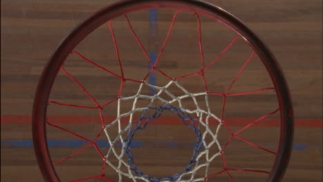 A-man-tosses-a-basketball-through-a-hoop-and-picks-it-up-when-it-bounces