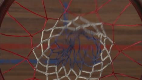 Una-Pelota-De-Baloncesto-Entra-En-La-Red-Y-Un-Jugador-La-Recoge