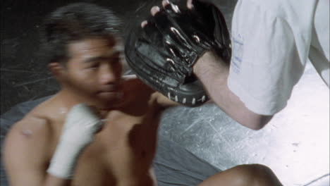 A-boxer-practices-punching-with-the-help-of-another-person-wearing-a-glove