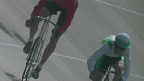 Two-men-ride-bicycles-one-makes-gestures-with-his-hand