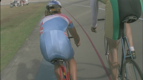 A-man-and-woman-ride-bicycles-around-a-track