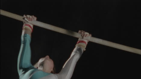 A-woman-performs-a-gymnastic-routine-on-bars