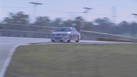 A-race-car-races-around-a-track-as-people-watch