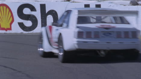 A-white-racing-car-races-around-a-track