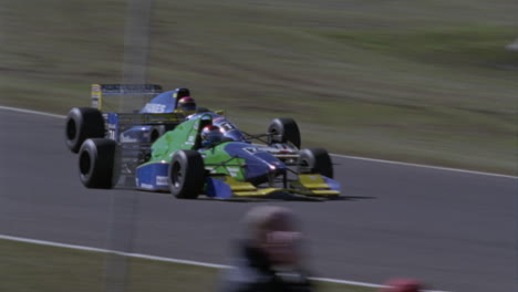 Racing-cars-round-a-turn-in-a-racetrack-people-move-around