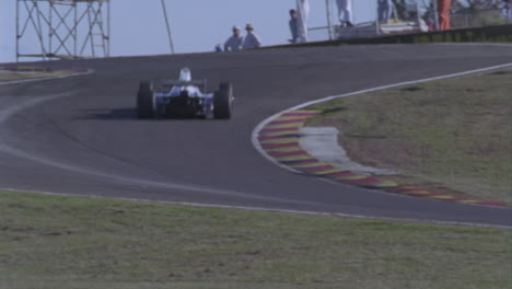 Racing-cars-race-around-a-track-as-spectators-watch