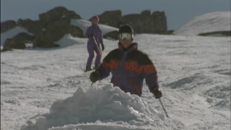 Three-people-are-skiing-one-jumps-over-a-mound-of-snow