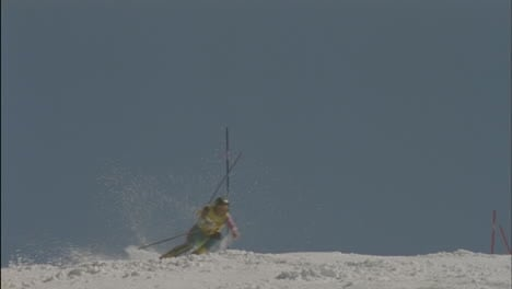 A-skier-skis-around-poles-hitting-one-and-continues-down-a-slope
