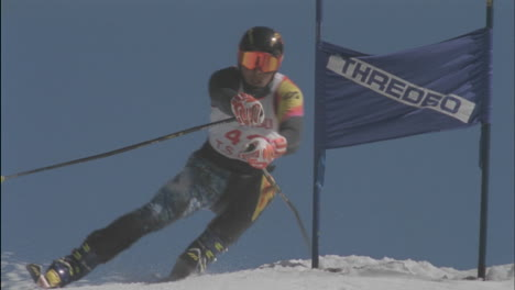 A-competitive-skier-passes-a-sign-as-he-skis-downhill