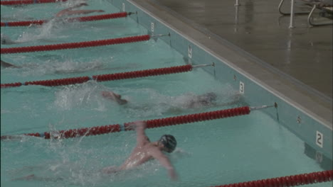 Male-swimmers-reach-the-finish-line-one-swimmer-raises-his-arms
