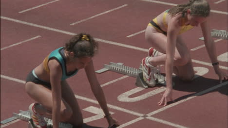 Several-women-runners-leave-the-starting-block-on-a-track
