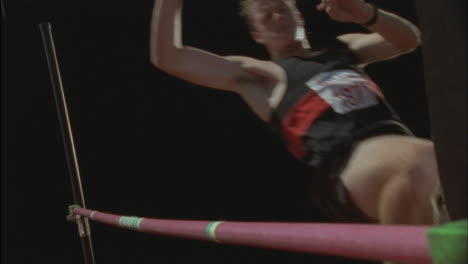 A-man-does-a-high-jump-knocking-the-pole-down