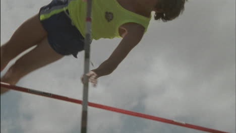A-young-man-does-a-pole-vault-lands-on-a-mat-and-stands-up-smiling