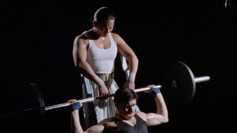 A-man-works-with-a-barbell-with-another-man-assisting-him