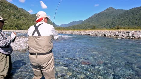 Guest-and-guide-catching-a-trout-while-fly-fishing-on-the-Huequi-River-in-Southern-Chile