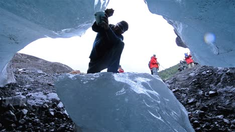 Low-angle-view-of-a-man-chipping-ice-from-Monte-Melimoyu-glacier-in-Southern-Chile