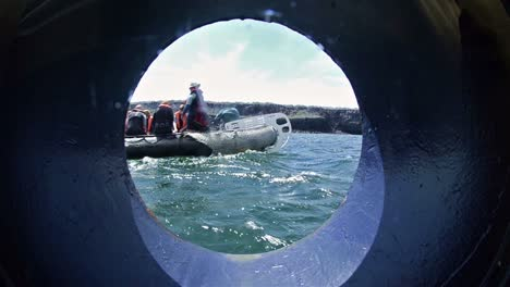 View-through-a-ship-s-porthole-of-snorkelers-departing-on-an-inflatable-raft-in-the-Galapagos-Islands