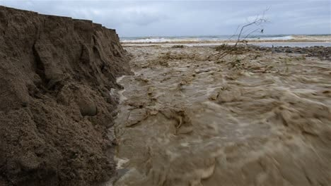 Low-angle-of-Sanjon-Creek-washing-beach-sand-into-the-ocean-after-heavy-rain-in-Ventura-California