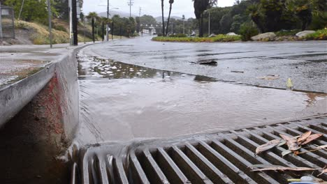 Water-flowing-down-a-street-gutter-into-a-storm-drain-after-heavy-rain-in-Ventura-California