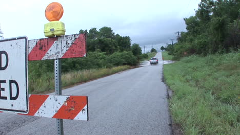 Ein-Fahrer-Ignoriert-Ein-Straßensperrungsschild-Und-Fährt-Durch-Ein-überflutetes-Gebiet