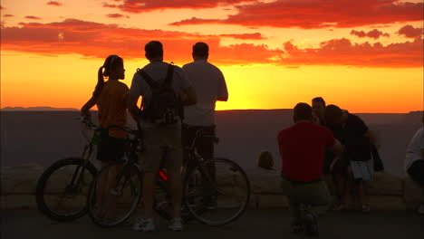 Tourists-On-Bicycles-Pause-At-The-Rim-Of-The-Grand-Canyon-At-Sunset
