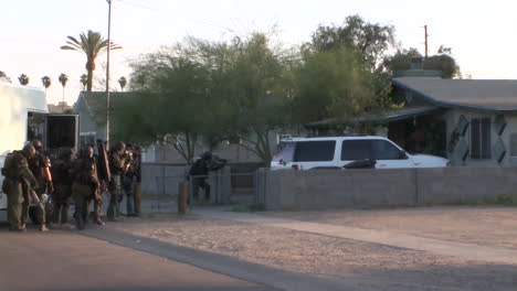 A-Swat-Team-Raids-A-Suspected-Drug-House-With-Weapons-And-Guns-Drawn