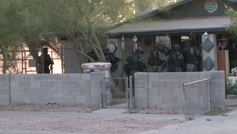 A-Swat-Team-Raids-A-Suspected-Drug-House-With-Weapons-And-Guns-Drawn-1