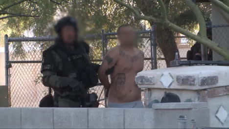 A-Swat-Team-Takes-Suspects-Into-Custody-From-A-Drug-House