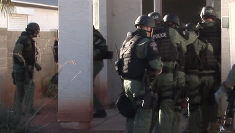 A-Swat-Team-Raids-A-Suspected-Drug-House-With-Flash-Grenades-And-Guns-Drawn
