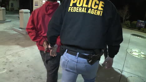 Federal-Agents-Handcuff-And-Lead-Away-A-Suspect-For-Drug-Crimes