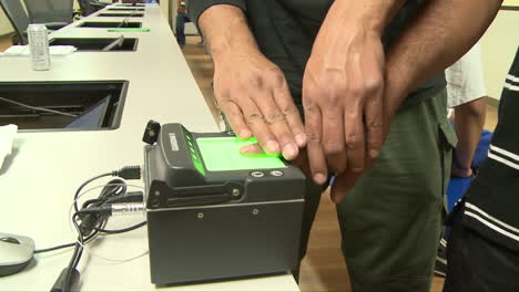 Federal-Agents-Fingerprint-A-Suspect-At-A-Detention-Facility