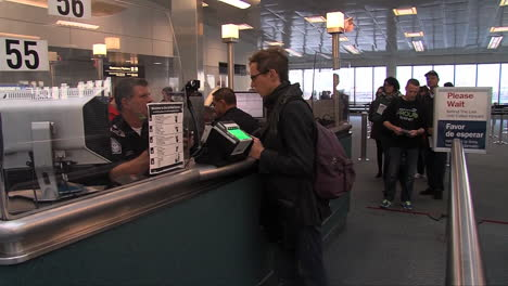 Arriving-Passengers-Passports-Are-Checked-By-Homeland-Security-At-An-Airport-2