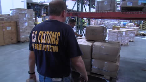 Homeland-Security-Agents-Search-Through-A-Warehouse-In-A-Shipping-Facility