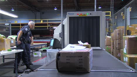 Homeland-Security-Agents-Inspect-Packages-In-A-Shipping-Facility